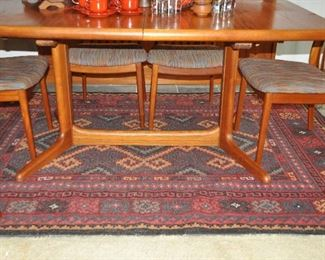 "Fabulous base design of the dining table. Shown with a hand made 100% wool area rug in red, gold, gray and black, 7'8"" x 5'5""."