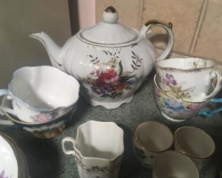 Musical tea pot, along with collection of bone china tea cups and saucers.