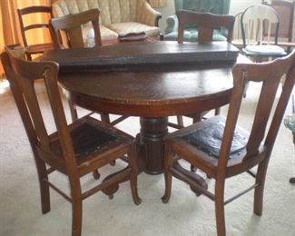 Round pedestal oak table with three leaves and four T back chairs.
