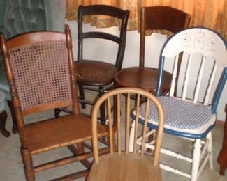 Caned antique sewing rocker, child's antique chair, and three other antique chairs.
