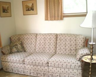Nice beige sofa with a tiny print, metal table lamp combination. Two matching prints, lots of wall art.