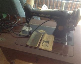 Antique singer sewing machine in the cabinet.  Has original instruction book.
