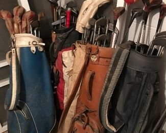 Several bags of vintage golf clubs.
