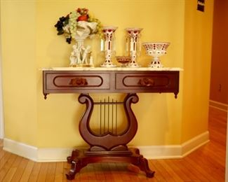 """Marble top table 37.5"""" wide by 15"""" deep by 29.5"""" tall. Red glass items sold."""