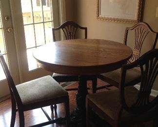 Round oak Breakfast table with black cast iron pedestal. 4 chairs are separate.