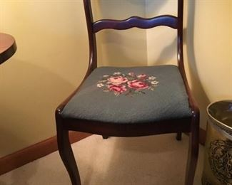Antique chair with needlepoint seat cover.