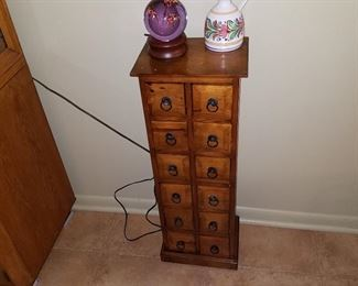 Cute 12 drawer stand. Paperweight is on a lighted base
