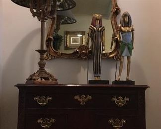 Queen Anne occasional table; gilded mirror; table lamp; Egyptian figurines