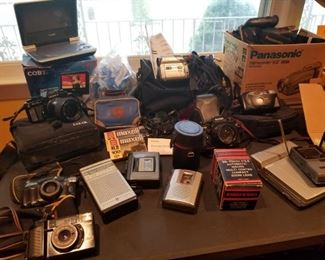 Packed Table of Vintage cameras, cassette players, DVD and Cd players/viewers, Video Cassette recorders, Miniature VHF/UHF Casio TV, Complete Kodak Easy Share Camera and Printer, etc