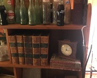 Some of the many leather bound books, bottles, clocks
