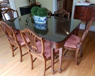 Beautiful mahogany Duncan Phyfe Style dining table and 6 Shield back chairs. 5 chairs, 1 armchair. One leaf not shown, glass top.