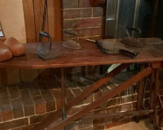 Showing (1) 3 flat cast iron pressing irons, various sizes; (2) vintage wood, leather and brass Eagle fireplace bellows fire stoker; (3) rustic wooden antique ironing board with iron rest sole plate and (4) pair of wooden shoes from Amsterdam.