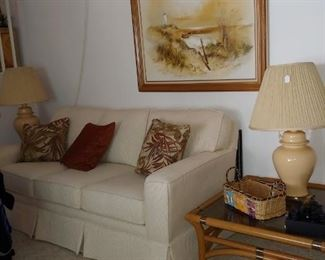Cream Upholstered Couch, Lamps, Artwork, Rattan Coffee Table
