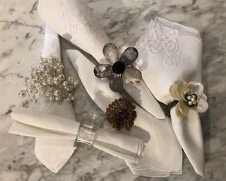 A variety of napkin holders in large quantities. Hem-stitched, linen and lace, oversized dinner napkins.