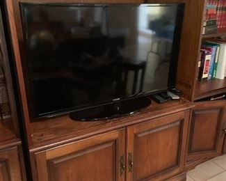 Large flat screen in wooden entertainment center