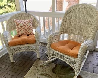 There are several pieces of white wicker furniture