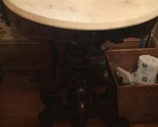 Marble top black maple round table with wheel feet $375