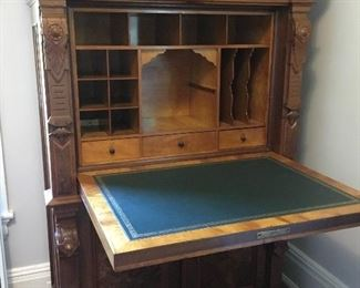 Gorgeous secretary with intricate carving and storage and leather writing surface