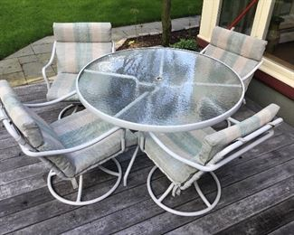 Glass circular patio table and 4 swivel chairs