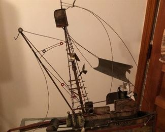metal sail boat .  there is a metal sail that attaches to it.