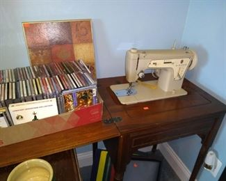 CDs and Singer sewing machine in cabinet