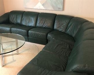 Leather Sectional couch and glass and chrome round coffee table, and large acrylic artwork