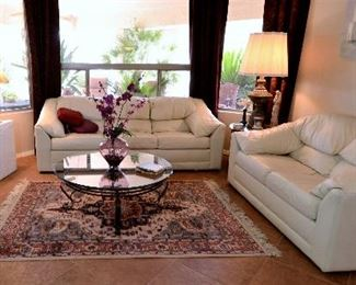 Soft white leather sofas. Round glass coffee table and rugs for sale.