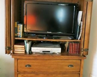 Entertainment stand w/ 3 drawer storage, flatscreen TV, misc. books, CD's, etc.