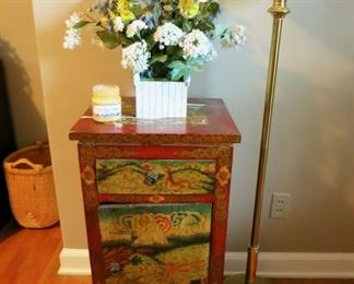 Wooden cabinet, floor lamp, silk flower arrangement