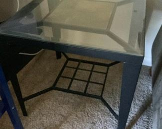 There are 2 glass end tables with stone inserts