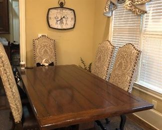 Farmhouse table with six upholstered chairs with leather seats.
