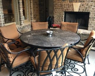 Round patio table with six chairs & scroll rug create a warm & comfortable dining environment.