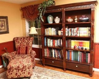 View of bookcase with chair and ottoman.