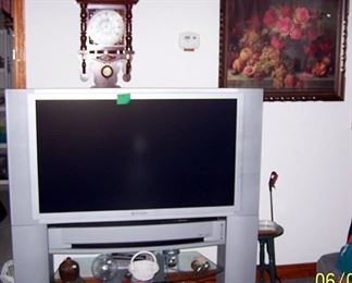 Nice wall clock, older picture and large screen TV
