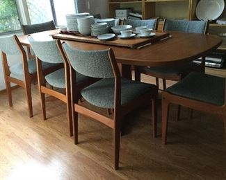 Mid Century Modern Danish Modern dining table shown with one leaf in table and one on top, with ten chairs! With the additional leaf put in they all fit around the table. Upholstery in good condition.