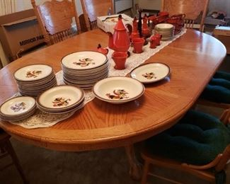 An Oak Table and 6 Chairs with Leafs that has basically never been used. A collection of wonderful Colorful 'Poppy Trail' Rooster Pottery Dishes from California.