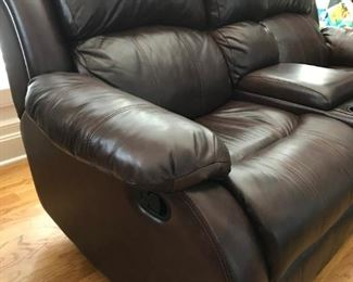 Brown leather reclining / rocking loveseat with storage center