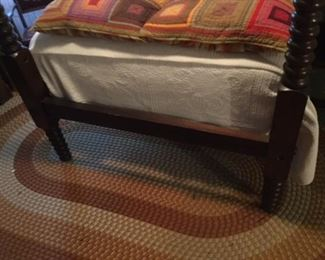 end of the bed and better view of braided rug