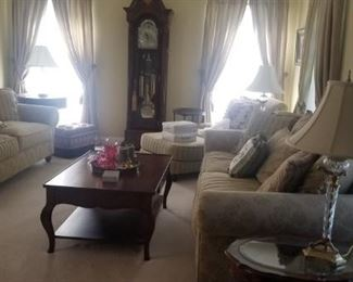 Formal Living room with Grandfather clock , wooden tables, lamps and wall art. Barely sat in this room