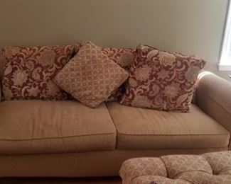 sofa and love seat with many pillows and ottoman
