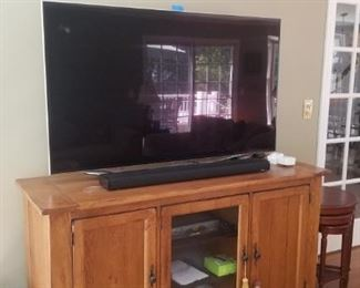 """Large flat screen tv and Wooden TV stand that is 63"""" across 36"""" high and 22"""" wide"""