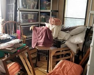 Craft room full of yarn, sewing materials, knitting machine, large plastic storage containers, plastic storage shelving and more.