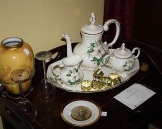 Very nice magnolia tea set on a nice, wooden table.