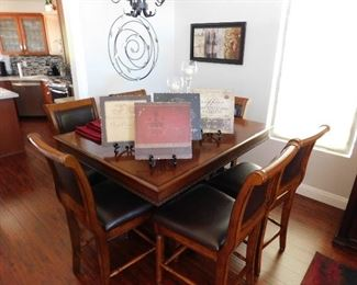Legends Dining table with hidden table leaf and 6 leather chairs, counter height.