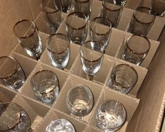 25 champagne glasses with gold rims.