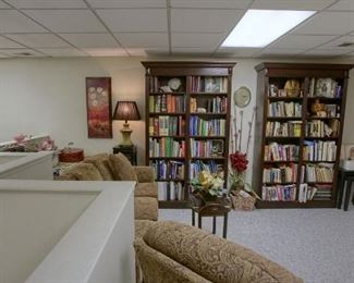 Books and bookshelf, couch and chair, home decor and artwork is for sale.