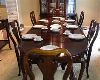 Thomasville cherry dinning room furniture, includes table with two leaves (seats 6 without leaves, up to 12 with both leaves comfortably), four straight chairs, two arm chairs, lighted glass 4 door china cabinet/breakfront, tea cart with drop down sides and shelf.   Pictured with white and gold band German China