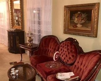 Antique Rosewood velvet sofa with three cushion medallion back and framed art.  French carved tea table with glass tray, cherry table, antique framed mirror and painted console chest