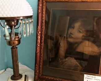 Antique brass lamp with crystals and milk glass shade.  Also very old photograph of unknown young woman