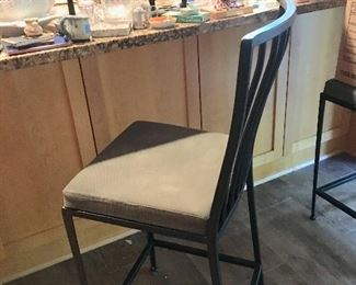 One of two iron counter stools with matching desk chair